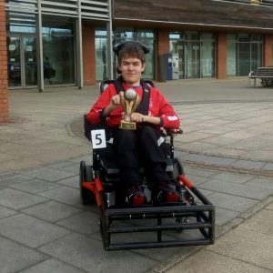 A man wearing a red jacket, sat in a Powerchair Football chair, outside a sports centre, holding a trophy.