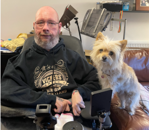 A man with a beard and glasses in a powered wheelchair, sat with him a dog
