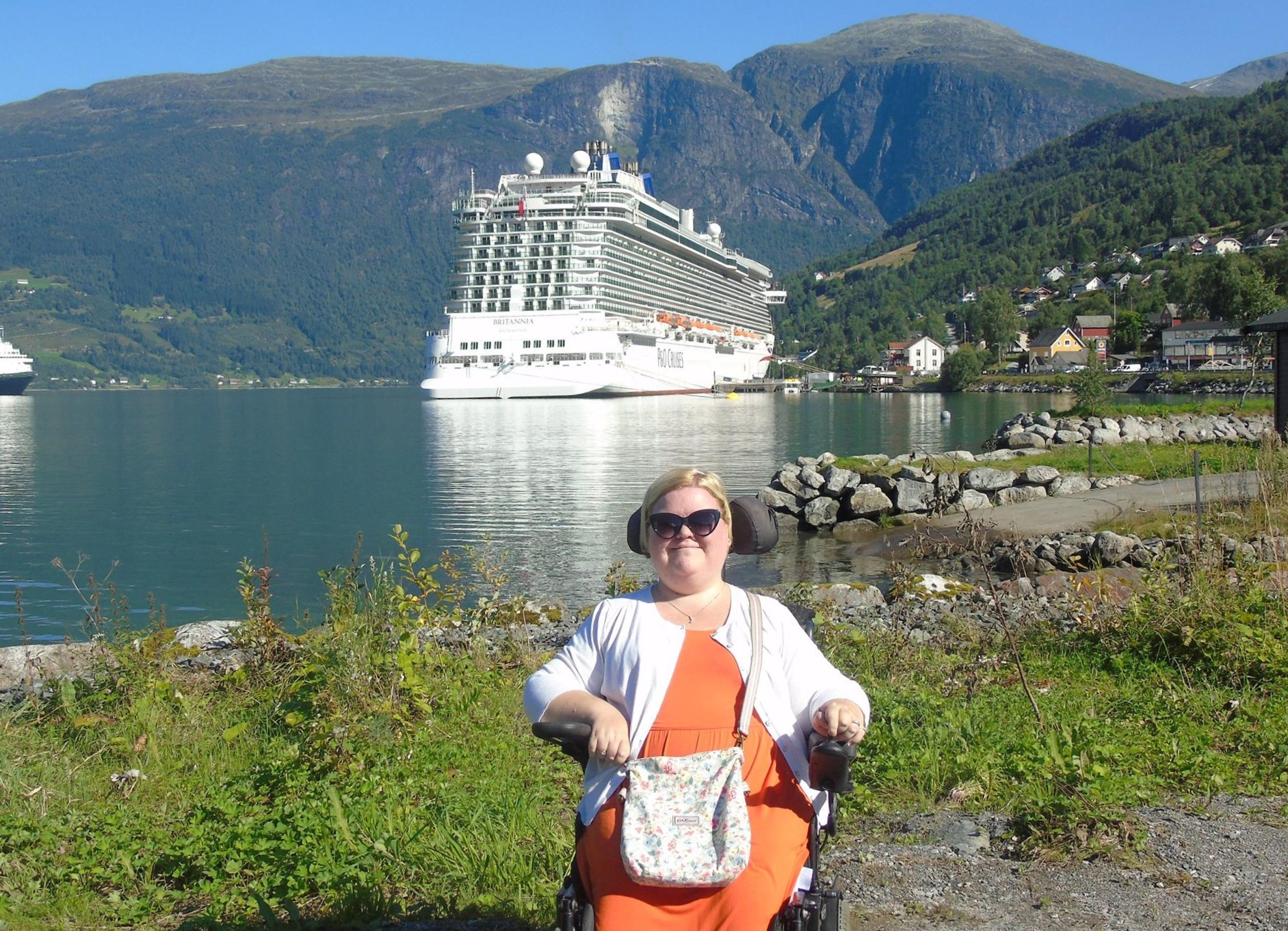 Lady sat on a powerchair wearing sunglasses in front of a cruise ship with mountains behind