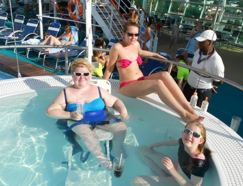 Blond haired woman in a blue swimsuit wearing sunglasses sat on pool hoist in a hot tub on a cruise ship deck holding a drink. A woman in a pink bikini sat on the side of the hot tub and young girl in the hot tub wearing a black t shirt and sun glasses.