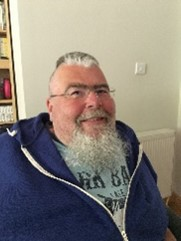 Julian Fiorentini, a white man with grey hair and a long grey beard in a blue zip-up jumper over a pale blue t-shirt