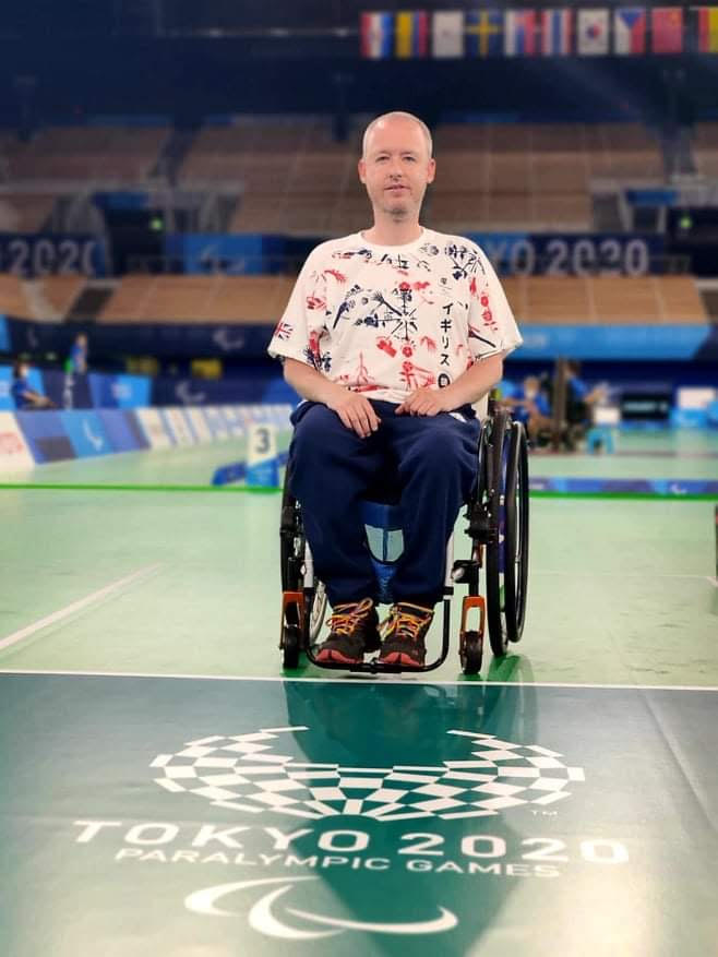 Stephen is sitting in a wheelchair in the centre of the Arena with his GB kit on