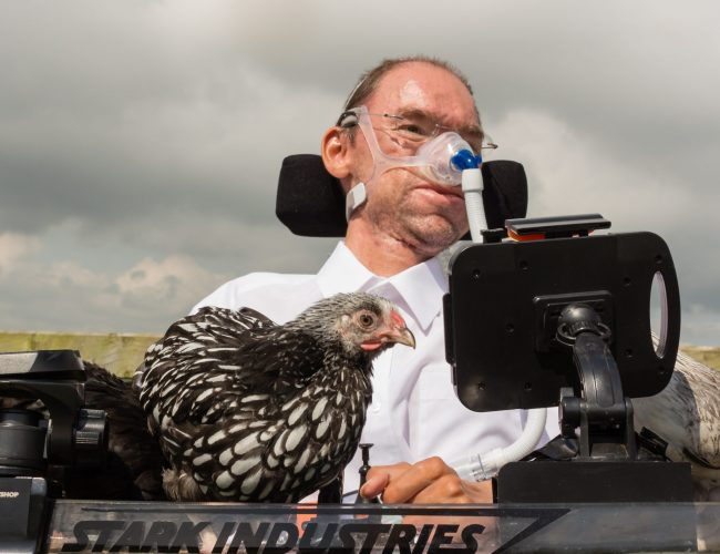 Daniel Baker with a chicken sitting on his wheelchair tray while on holiday in Wales