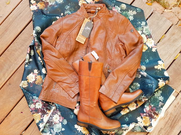 braune Lederjacke und Stiefel auf geblümtem Stoff, die Mode des Herbstes 2018