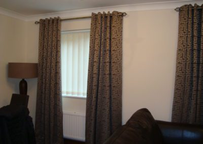 Vertical blinds and brown eyelet curtains