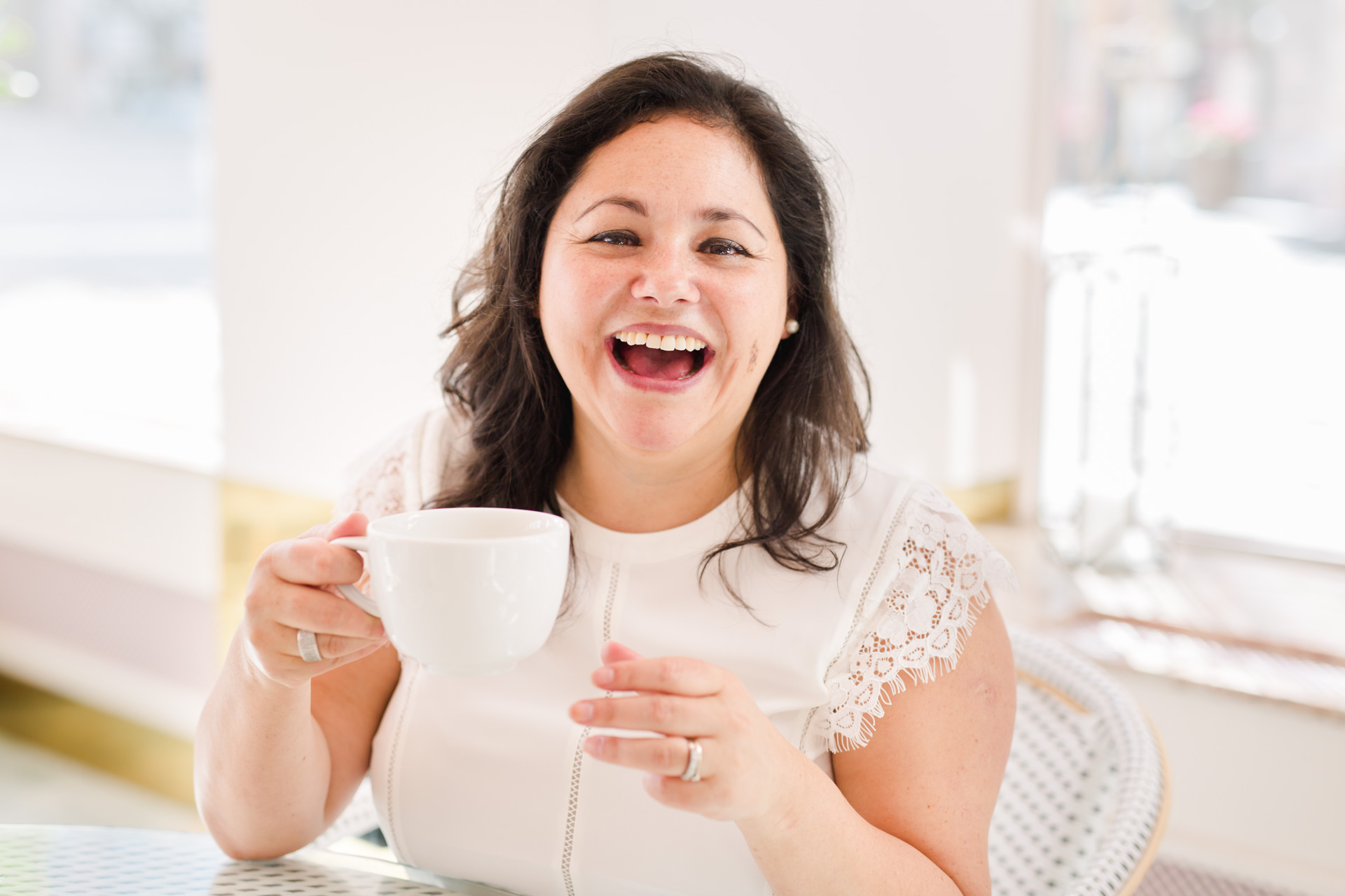 A branding photo of entrepreneur Marjorie Soto Diaz laughing and holding a cup of tea