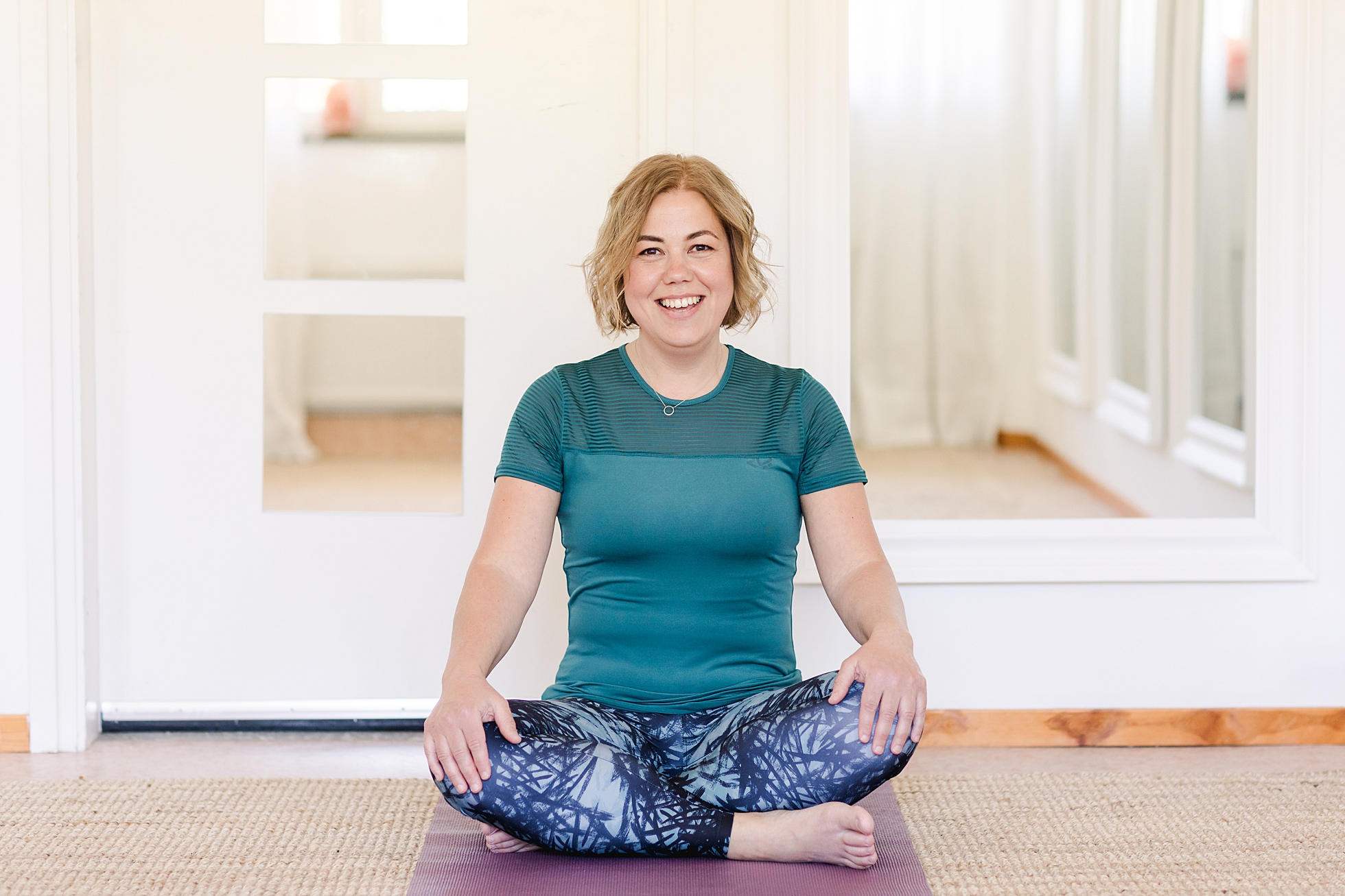 A yoga instructor sitting and smiling