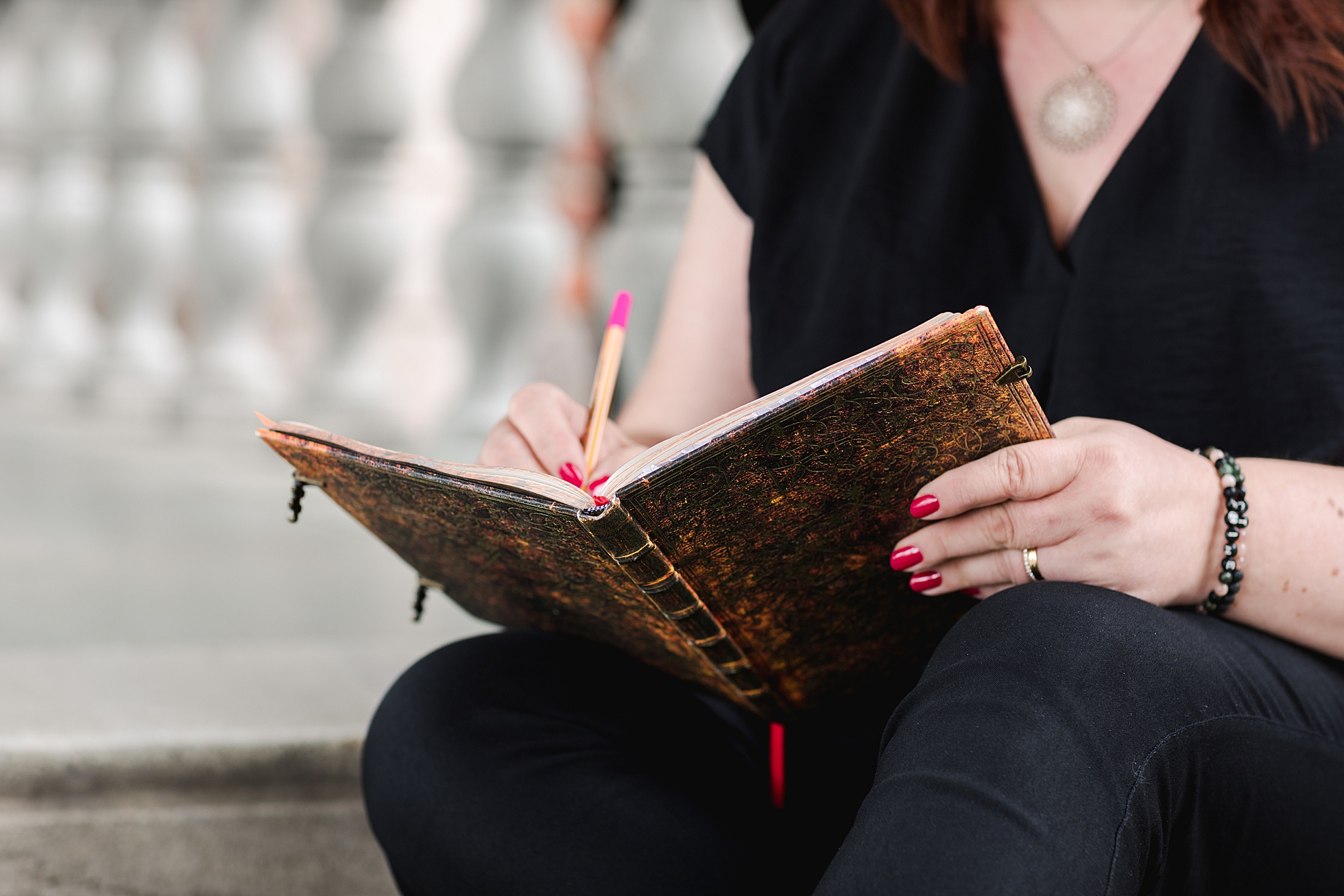 A close up photo of a woman writing in a notebook