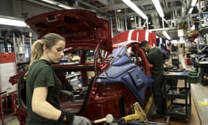 Employees works on a Jaguar automobile on the production line at Tata Motor