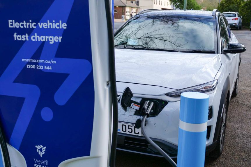 Electric car with charger in foreground.
