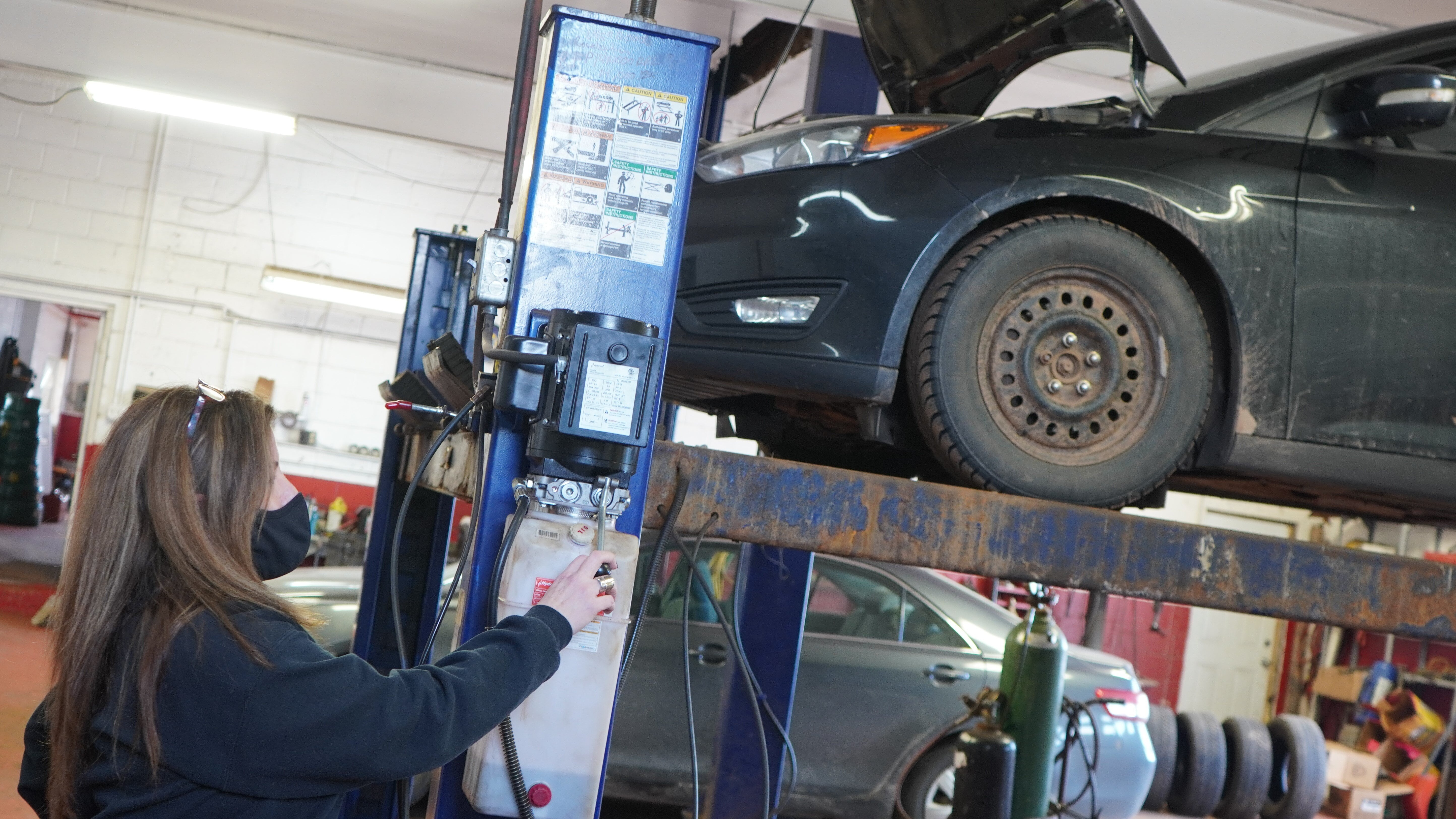 Lisa MacIntyre, owner of Her Man's Shop, hoists a vehicle up in her auto shop in Morell on Jan. 21 - Daniel Brown/Local Journalism Initiative Reporter