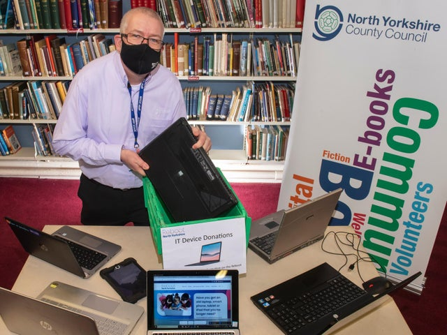 Mark Glossop from Scarborough library with dropped-off laptops and the Reboot North Yorkshire website.