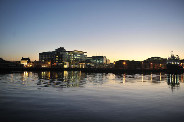 Dusk at  Cork city quays, showing Navigation Square and the now vacated Cork Bonded Warehouses at the Port of Cork site.