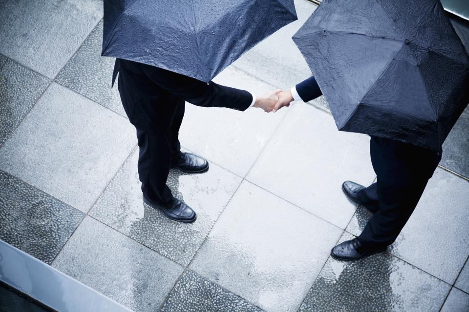 High angle view of two businessmen holding umbrellas and shaking hands in the rain