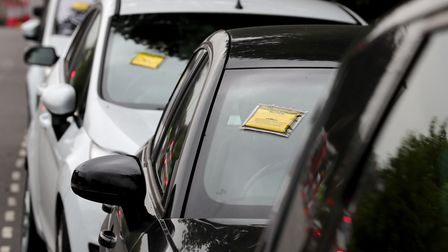 Penalty charge notices affixed to several cars left in restricted parking bays on a road near Gatwic