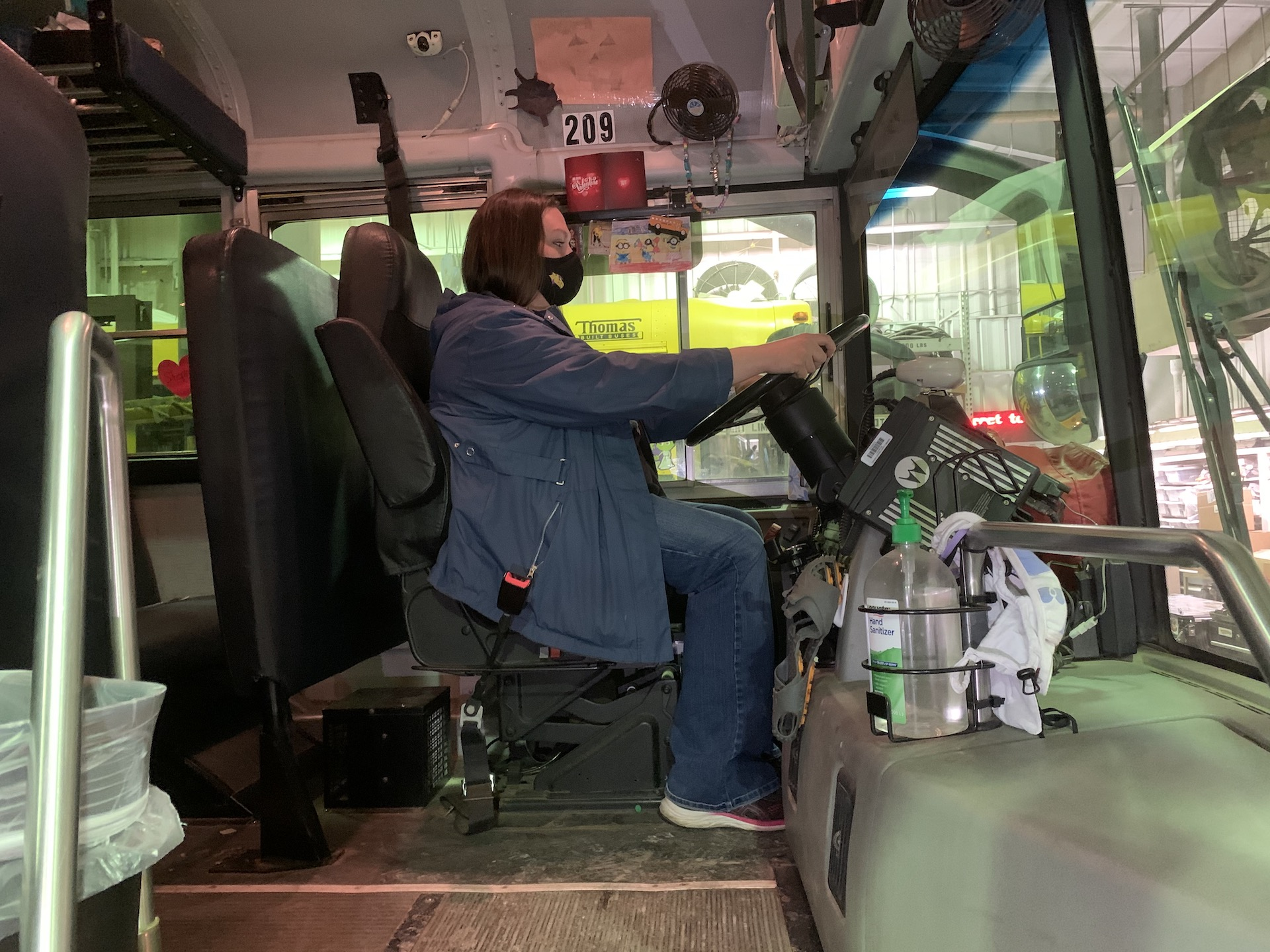 School Bus Driver Timarie Javier wears a face mask while sitting behind the wheel of a Campbell County School District bus in Gillette, Wyoming. The district started transporting students at the start of the 2020-2021 school year, with safety protocols in place to mitigate COVID-19 exposure.