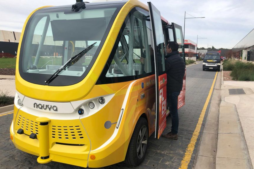Man stands at open doors of an autonomous shuttle bus is launched at Flinders University in Adelaide.