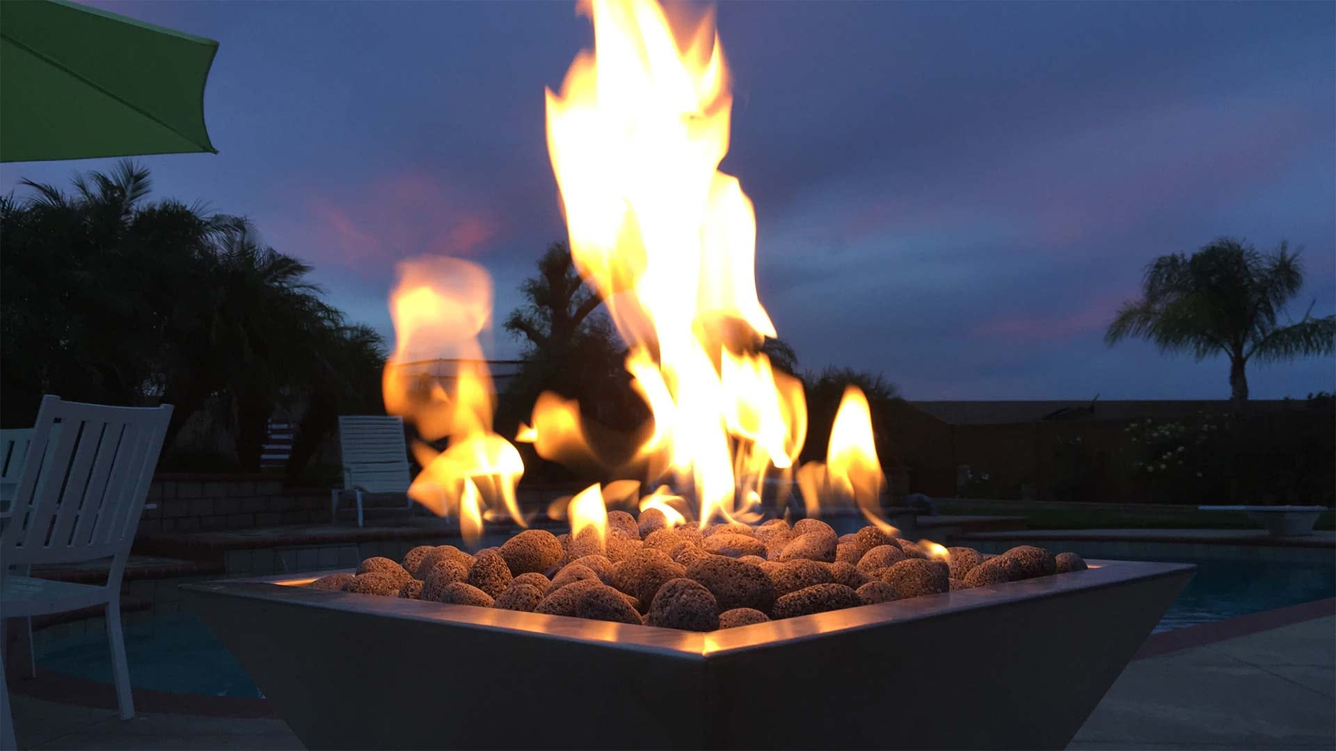 A backyard fire table loaded with lava stones.