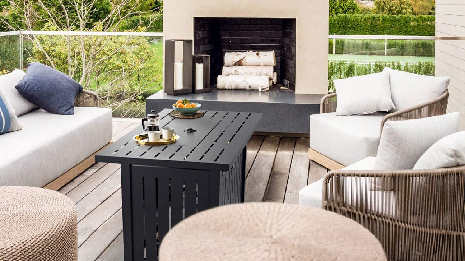 A rectangular SNAN fire table placed in the middle of lovely off-white patio furniture outdoors, with a couple coffee cups and a French press coffee maker.