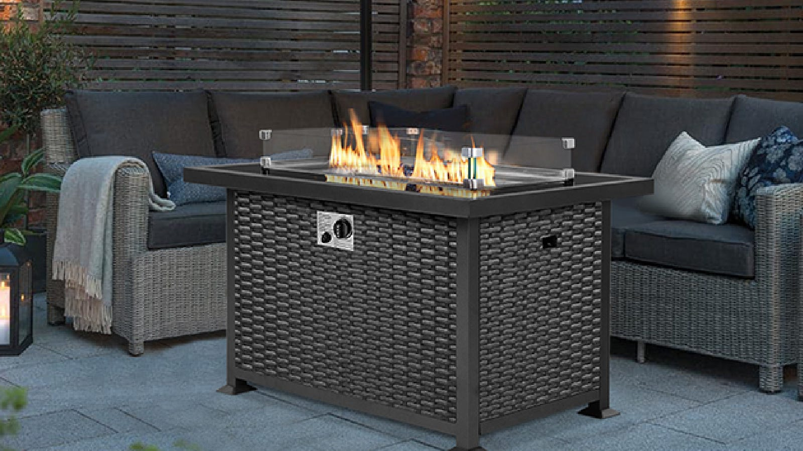 A lovely rectangular shaped fire table by U-Max, fit nicely in the middle of sofa style patio furniture, in a cozy outdoor setting.