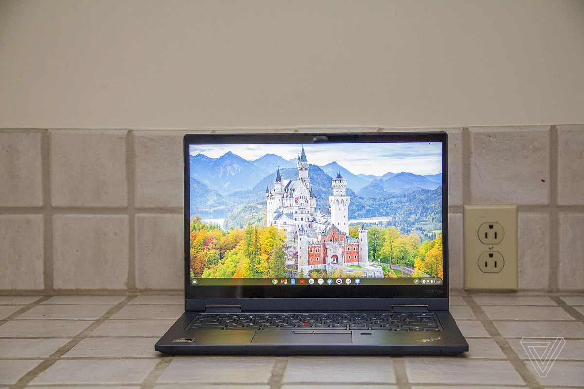 The Lenovo ThinkPad C13 Yoga Chromebook seen from the front on a tile counter. The screen displays a white castle surrounded by trees with mountains in the background.