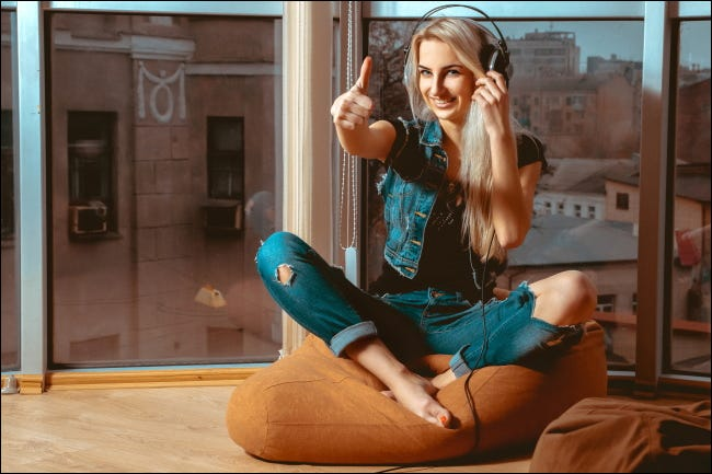 A woman listening on headphones and giving a thumbs up.