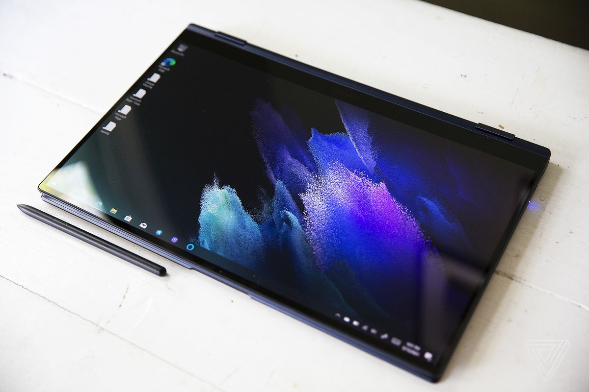 The Samsung Galaxy Book Pro 360 (15-inch) in tablet mode with the stylus below it on a white table. The screen displays a purple pastel pattern on a dark background.