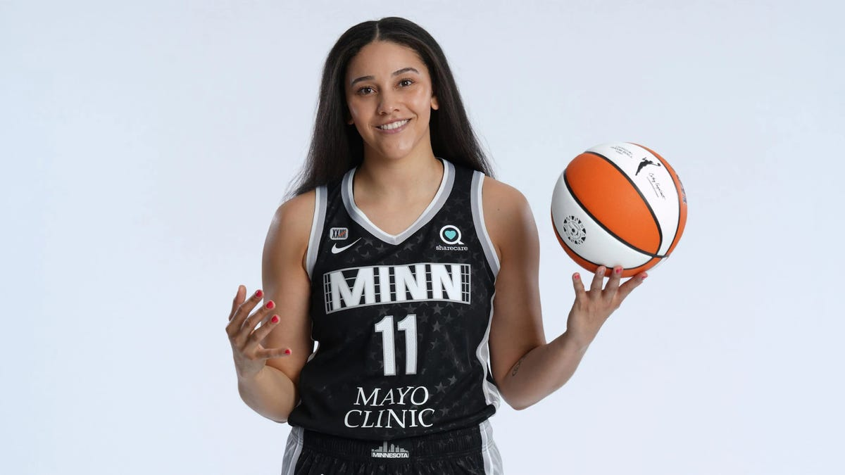 A WNBA Basketball player twirling a ball.