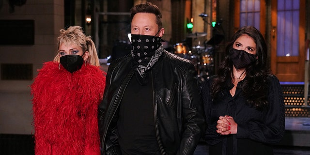 """""""Saturday Night Live"""" guest host Elon Musk appears with musical guest Miley Cyrus, left, and """"SNL"""" cast member Cecily Strong during a promotional video for the late-night show. (Getty Images)"""