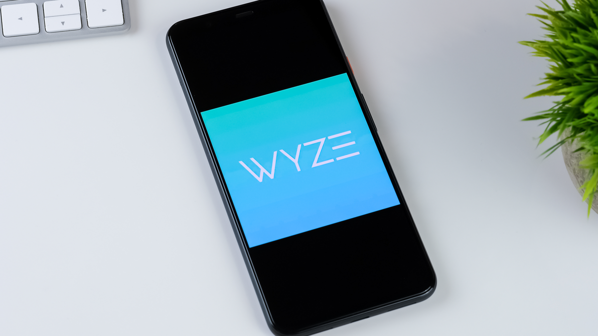 Wyze app logo on a smartphone screen laying on a desk with a keyboard and plant
