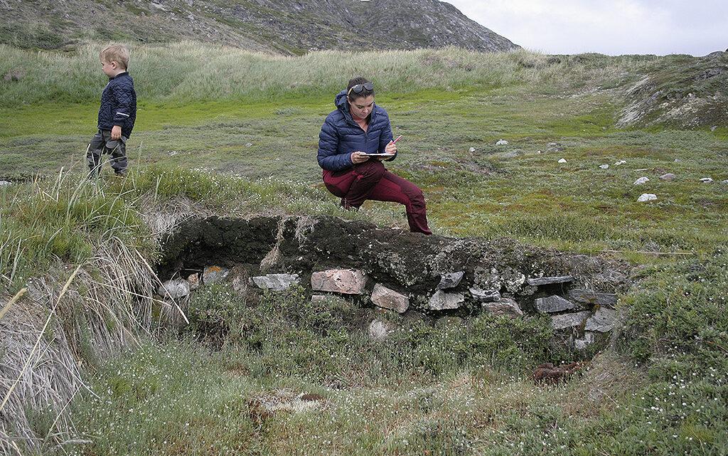 """Asta Mønsted og hendes søn skitserer et vinterhus, hvis bagvæg er meget tydelig i sin konstruktion. Bagvæggen var ifølge inuitiske fortællinger husets """"rumpe"""", hvorigennem døde blev båret ud, som en del af begravelsesritualet (foto: Asta Mønsted)."""