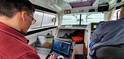 Inden for i kabinen hos Aron Aqqalu Møller fra Aasiaat. Aron Aqqalu fører båden, mens Aqqaluk Sørensen holder styr på opmålingerne. Som lokal har Aron Aqqalu livslang erfaring med at navigere i farvandet til stor fordel for undersøgelserne (fra Pinngortitaleriffiks Facebookside).