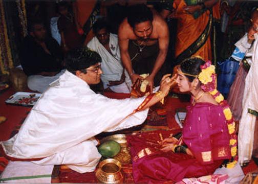 applying kumkuma on woman's forehead in marriage