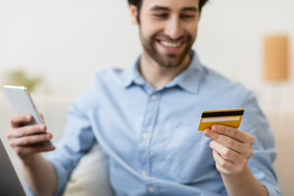 Happy man with smartphone and credit card shopping online indoors