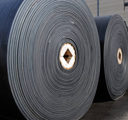 New industrial conveyor belts packed in rolls.
