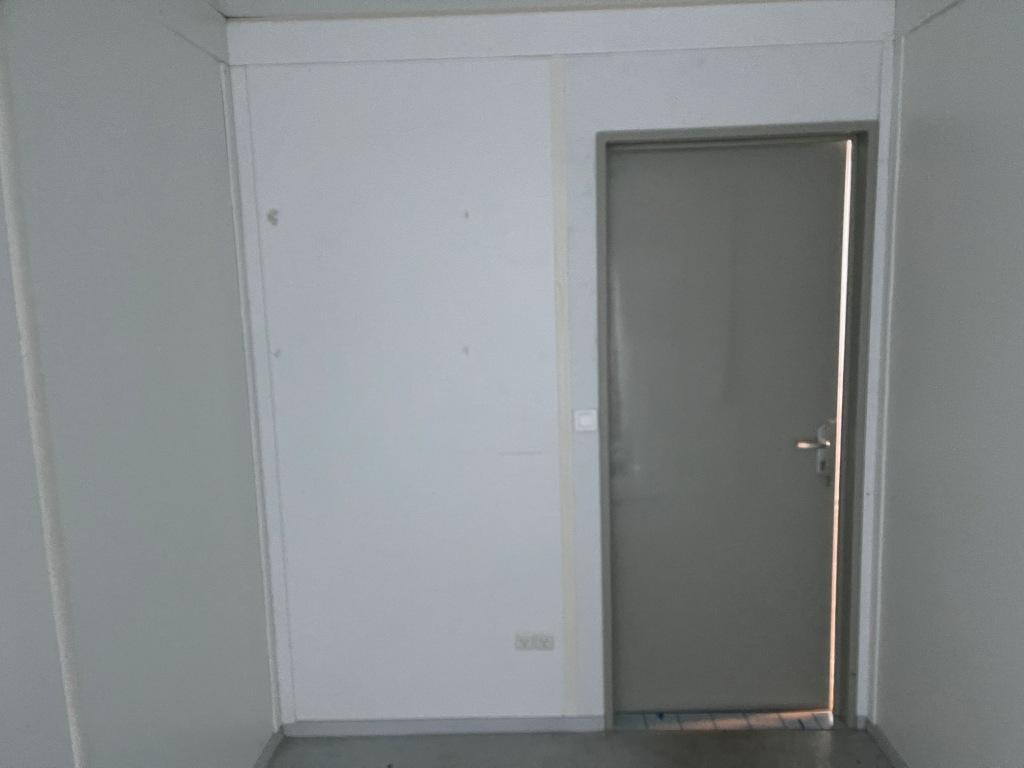 Kontorcontainer 20837659 set indefra. 20' har dimensioner: L: 6055 mm x B: 2435 mm x H: 2800 mm, lofthøjde på 2540 mm. Det er en brugt container fra 2008 i farven grå RAL 7032