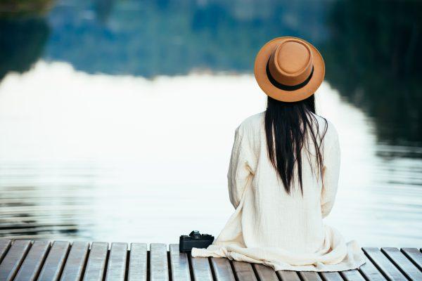 Kvinde sidder alene og betragter søen. Den sø af mennesker hun måske ikke kan nå ind til