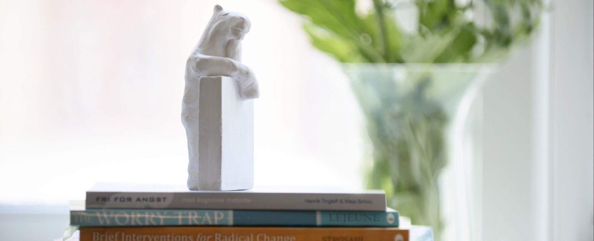 Figur af Læsehest ovenpå bøger om kognitiv adfærdsterapi, Acceptance and Commitment Therapy ACT og angst hos psykolog Maja Schou: Samtaler Terapi Supervision