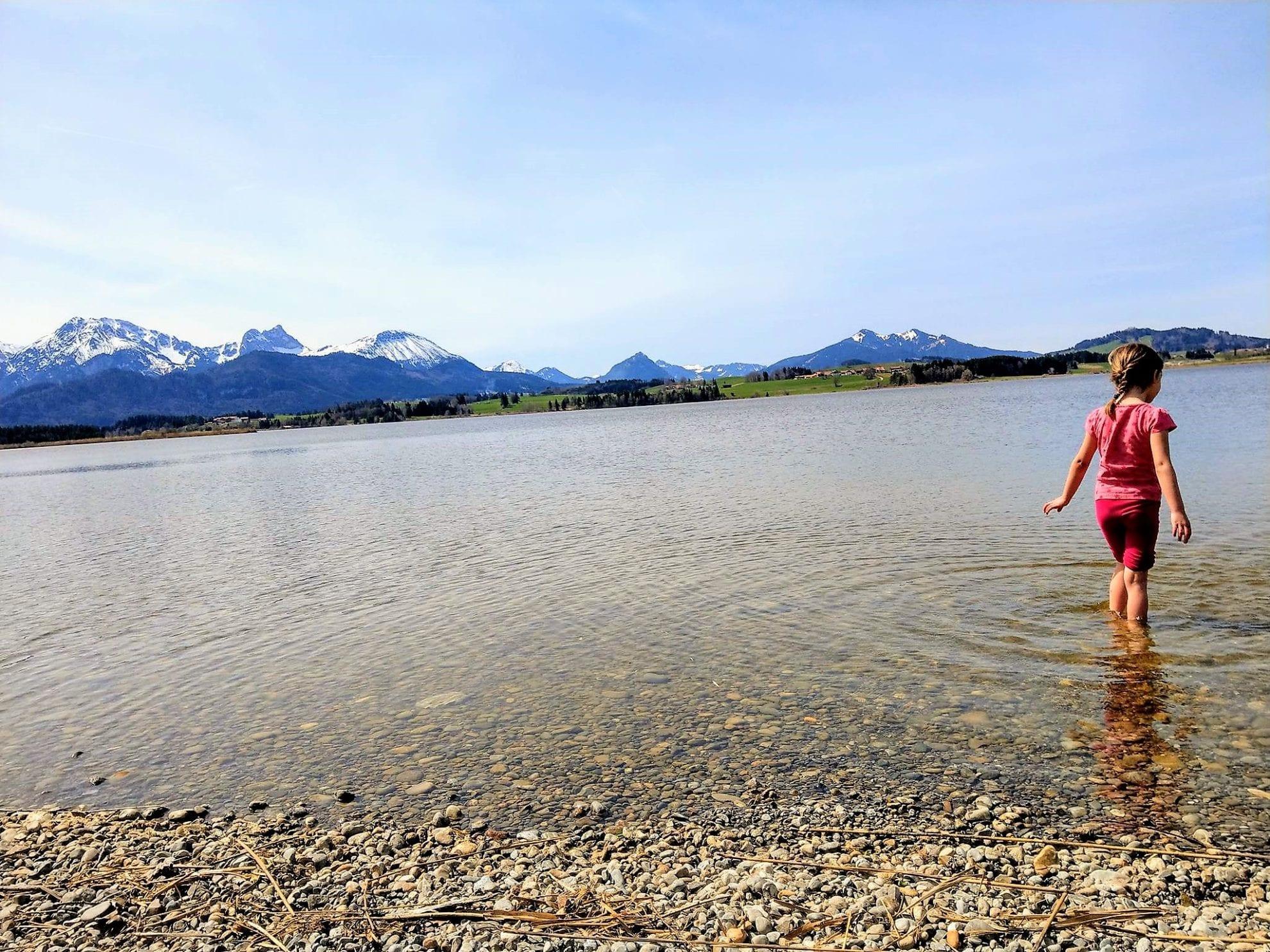 Ab ins kalte Nass und auf der Suche nach Muscheln im Hopfensee. Der Blick auf die Berge vollendet den Anblick