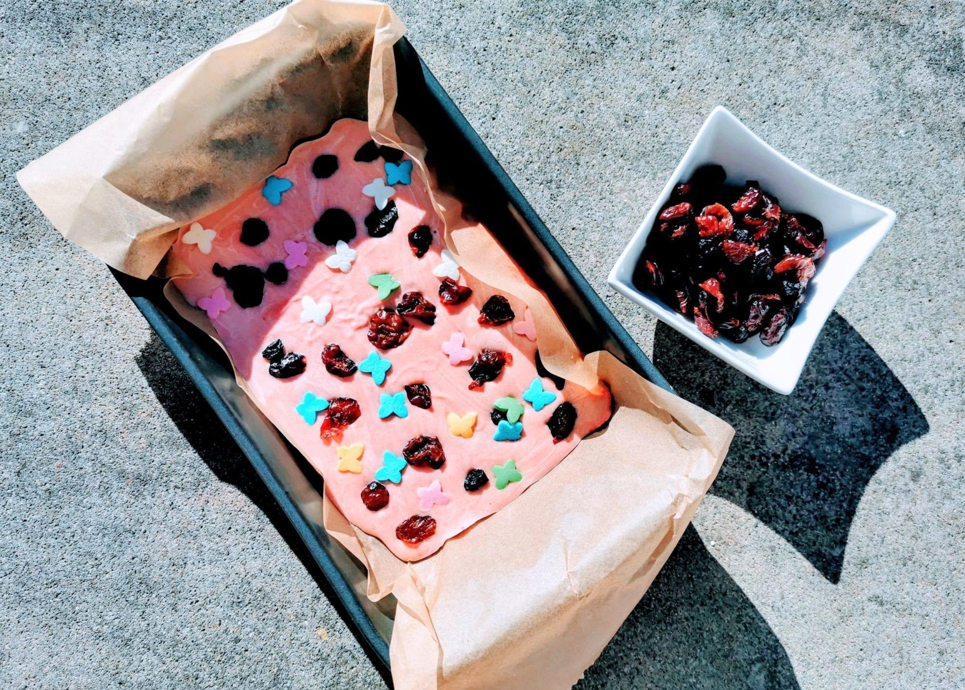 Geschenkidee aus der Küche: rosa Bruchschokolade mit getrockneten Beeren und Schmetterlingen. Ein einfaches Rezept aus nur 3 Zutaten auf Puddingklecks
