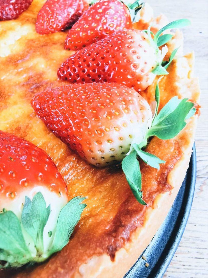 halbierte Erdbeeren auf dem Käsekuchen mit Heidelbeerklecksen - ein tolles Backrezept von Julie