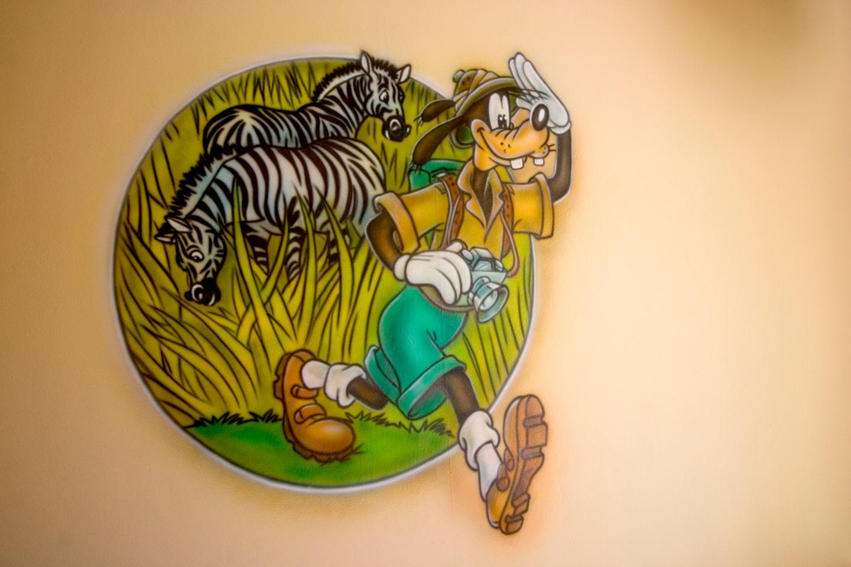 Goofy met zebra's airbrush muurschildering in safari kinderkamer