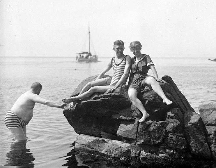 Män och kvinnor som sitter på klippor och badar i havet i mölle
