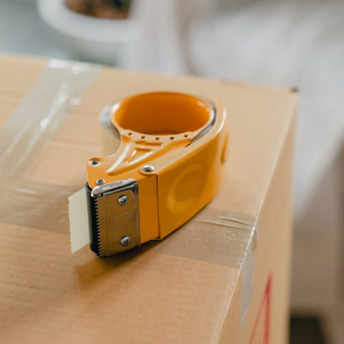 Canva - Packing tape gun on carton box