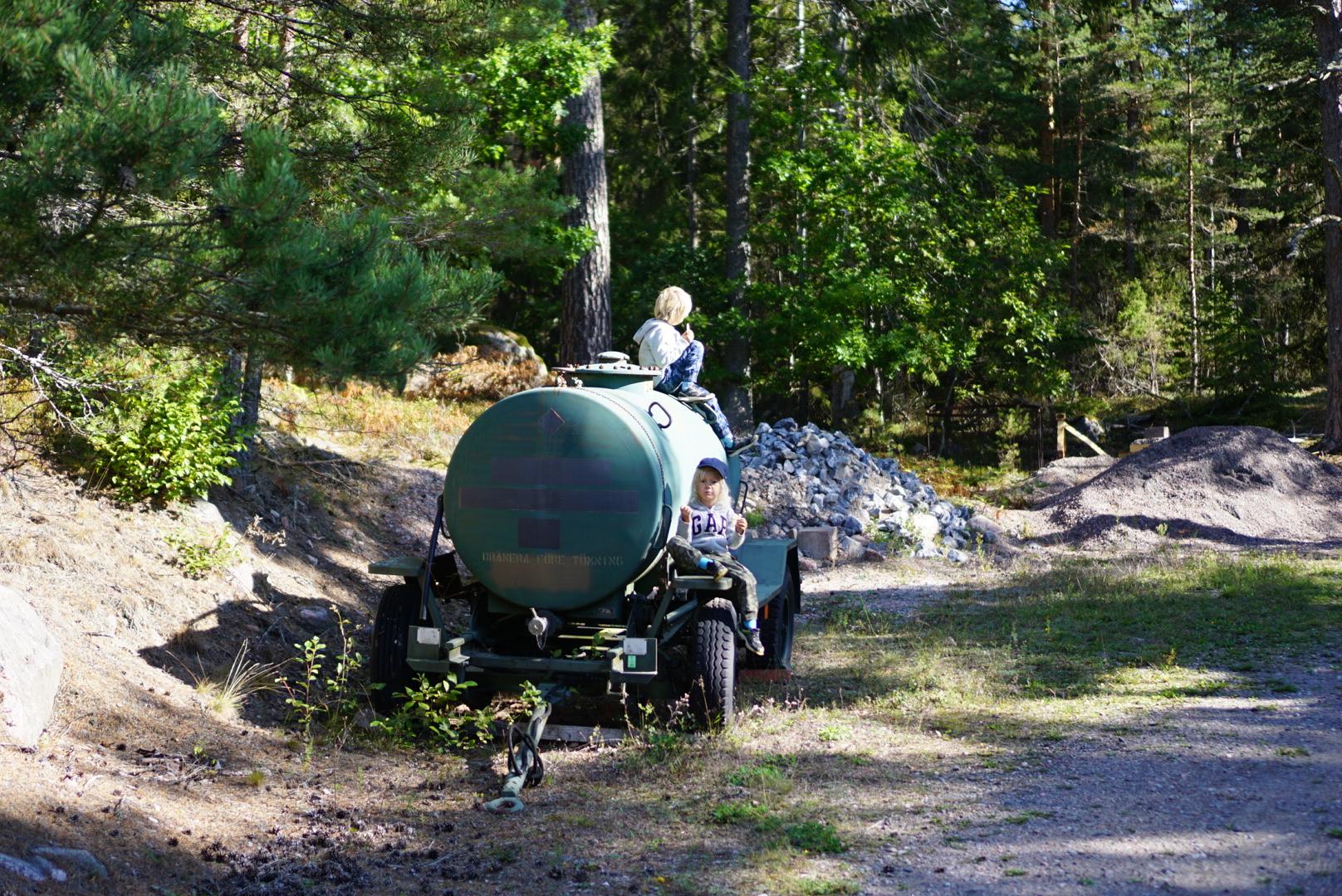 Barnen klättrar på gammal vattentank vid parkeringen till Stendörrens naturreservat.