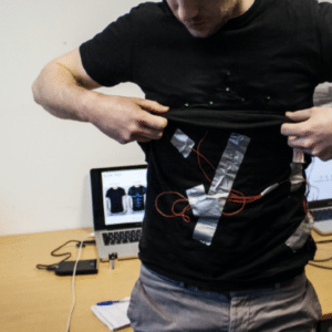 Arduino workshops; a student putting on an interactive prototype that is attached to his shirt