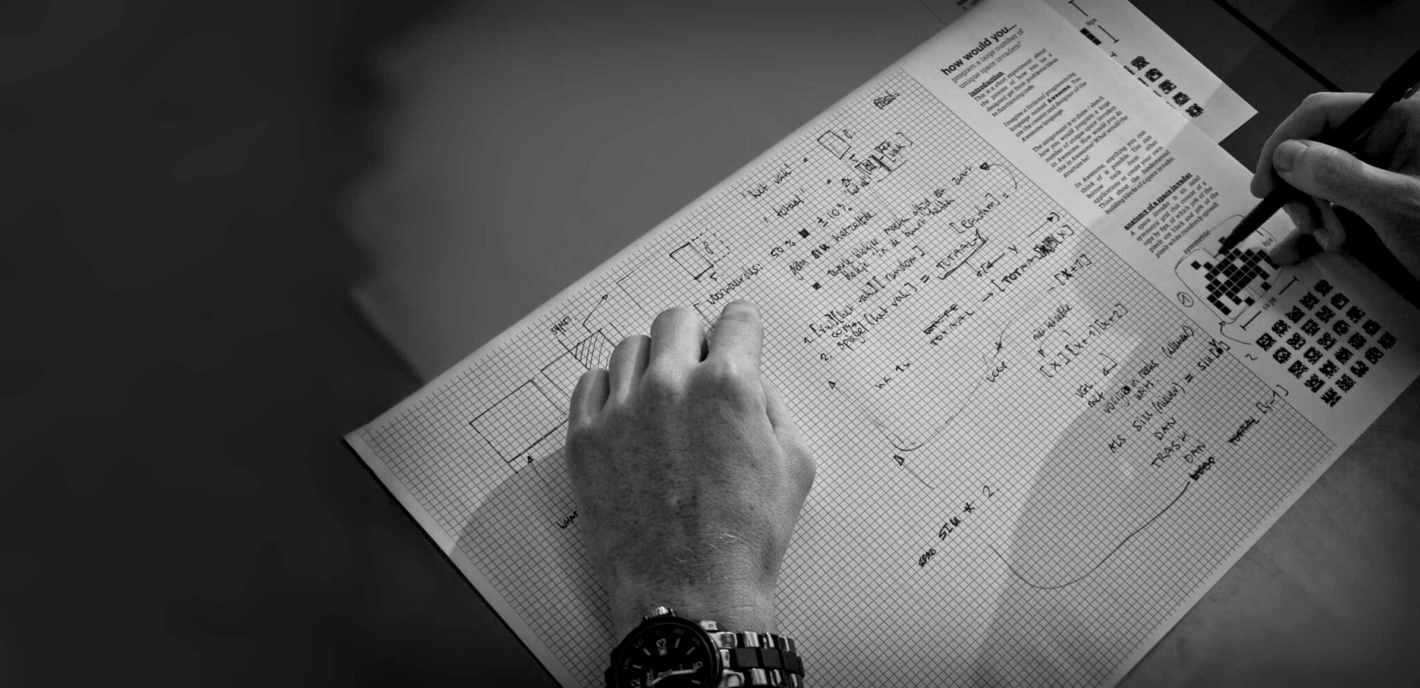 A photo of a person doing a paper programming exercise. The paper is full of notes and sketches.