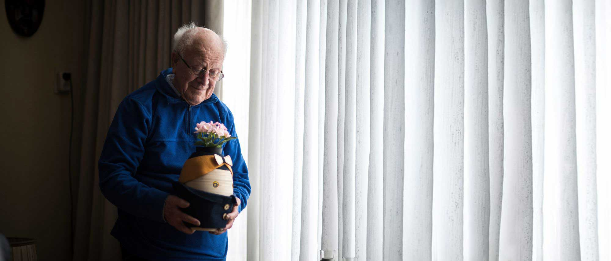 An older man holding the robot Tessa lovingly. He's standing in front of a window.