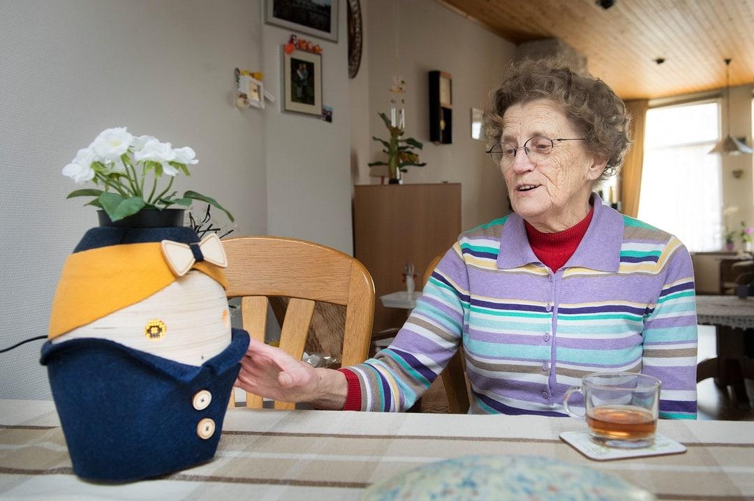 An elderly person touching her robot Tessa lovingly