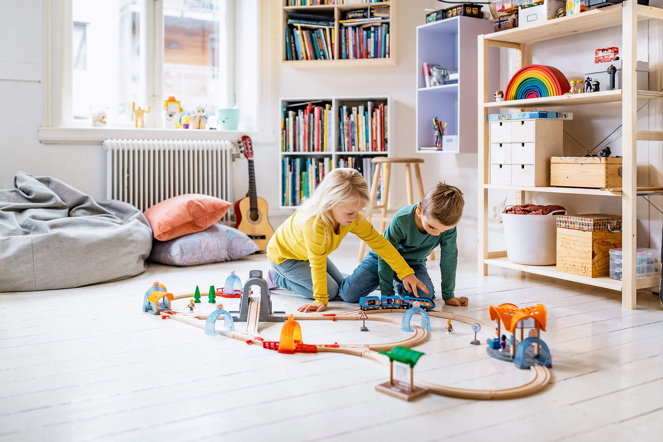 Kids playing with Brio trains on the floor, Kids room